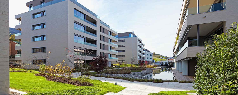 quartier d'immeubles modernes avec terrasse vitrées et sol au centre organique et végétal avec plan d'eau