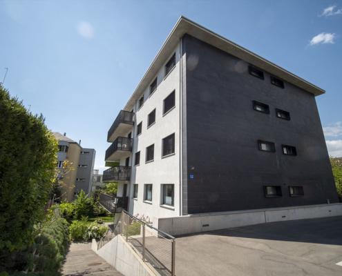 Façade d'un bâtiment gris et escaliers sur le côté gauche