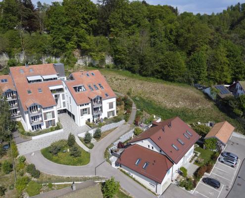 Quartier de maisons aux toits couleur brique avec parking sur la droite et forêt en arrière plan
