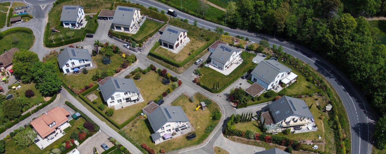 Vue aérienne d'un quartier de villas individuelles similaires avec toiture grise, jardins privatifs et panneaux solaires en bordure de route