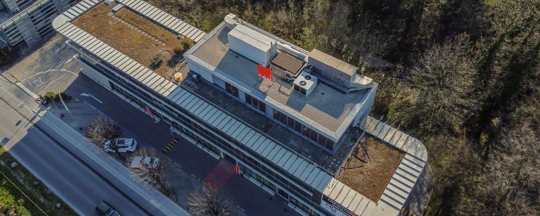 Vue d'avion sur immeuble commercial avec logo d'entreprise rouge sur le toit