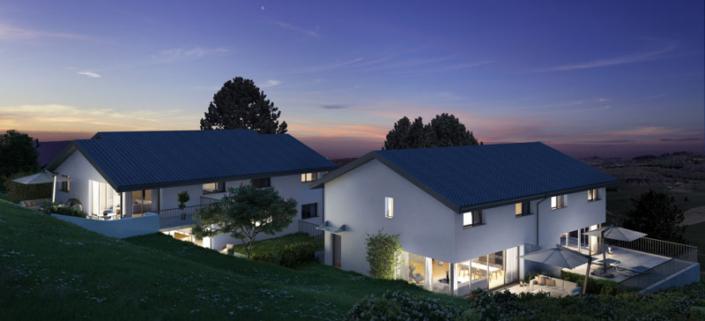 Vue sur deux villas au crépuscule avec lumière à l'intérieur et parasols ouverts sur les deux terrasses côté droit de l'image