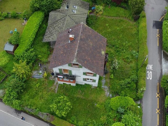 Vue aérienne sur maison au toit mensardé, façade blanche et volets verts, entourée de verdure