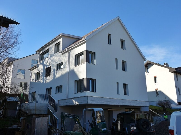 Façacade d'un immeuble blanc sans volets avec toiture mensardée
