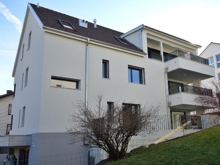 Façacade d'un immeuble blanc avec balcon et verdure