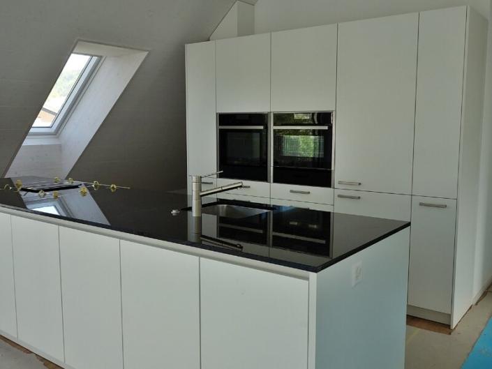 Cuisine blanche sous toit mensardé avec îlot centrat et plan de travail noir et velux à gauche