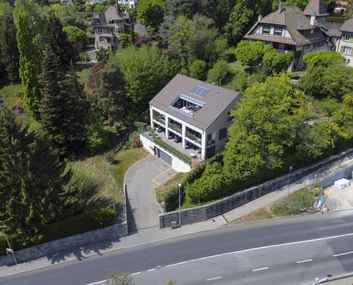 maison avec garage et panneaux solaire sur le toit et terrasse
