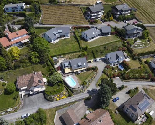 Vue du ciel sur quartiers de maisons avec jardins et piscines