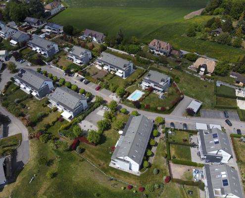 Vue du ciel sur quartiers de villas aux toitures grises mensardées et champ à l'arrière