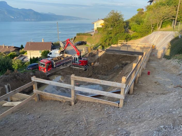"""Début d'un chantier pour le projet immobilier à Chardonne """"les Chardonnerets"""", lac léman sur le fond gauche de l'image, terrassement d'un terrain avec machine de chantier devant le lac et barrière de sécurité autours"""