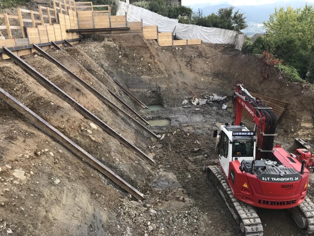 """Image d'un terrain avec un trou creusé dans lequel se trouve une machine de chantier en rouge sur la droite. Cela représente le nouveau projet """"Les Chardonnerets"""""""