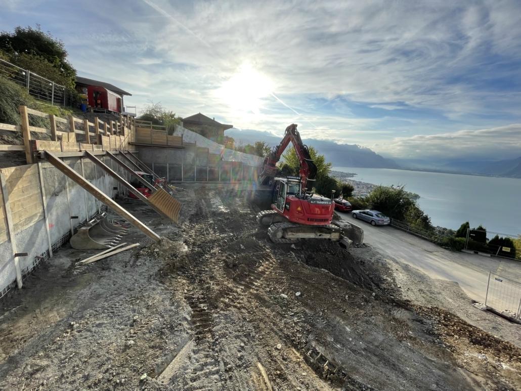 """Image d'un chantier """"nouvelle promotion les Chardonnerets"""" donnant sur le lac léman, machine visible à l'arrière"""