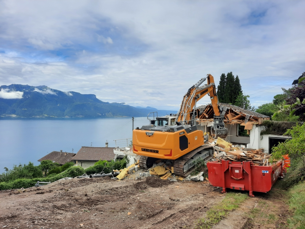 """deux machines de chantier, une orange, l'autre rouge devant le lac léman en fond, sol en chantier pour le nouveau projet à Chardonne """"Les Chardonnerets"""""""
